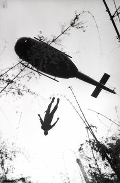 © Henri Huet, 1966, The body of an American paratrooper killed in action in the jungle near the Cambodian border is raised up to an evacuation helicopter, Vietnam