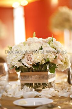 Low centerpiece vase wrapped with Raw Silk ribbon and rhinestone trim. Filled with white hydrangea, ivory, champagne and blush roses, ivory spray roses, ivory carnations, and white lisianthus. Photo courtesy of Catherine McKinley Photography.