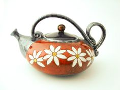 This teapot ishandmade in small art pottery studio in eastern europe.    Made of red clay and hand carved design.    The teapot is perfectly finished