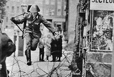 East German soldier Conrad Schumann jumping over the Berlin Wall on its third day of construction, at the time a barbed wire fence, as he defects to West Germany.    August 15, 1961.