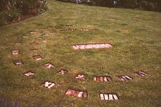 Simple Brick Human Sundial  with Hours & Months  -  Use bricks to create roman numerals, or numerals in stamped cement.  http://en.wikipedia.org/wiki/Norwegian_language  -  Because of tall grass, may need to make broad markers.