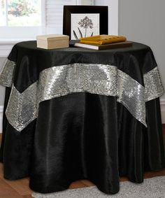 Dress the table in full finery with this layered tablecloth set. A sweeping black tablecloth provides the base, while an eye-catching sequin-embellished table topper offers a stylish sparkle.