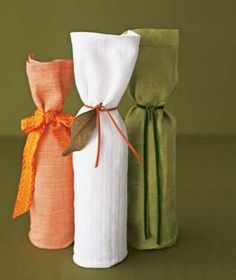 Place a wine bottle along one side of the fabric of a dish towel so that the bottle's top meets the top of the fabric. Fold the excess material at the bottom over the bottle, forming a pocket of sorts. Then roll the dish towel evenly and secure at the neck with ribbon.