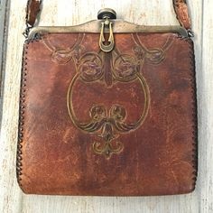 """Arts & Crafts hand tooled leather purse. Jugendstil or Art Nouveau. Measures 6 1/2"""" tall by 6 1/4"""" wide. Handle is 12"""" long and is broken and literally han"""