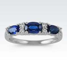 In a horizontal fashion, three oval traditional blue sapphires (approx. 1.26 carats TW) are featured in the band design of this ring. Eight round diamonds (approx. .15 carat TW) provide a brilliant accent to the sapphires as they are spaced between the three-stone design. This ring is crafted of quality 14 karat white gold, measures 4mm wide, and has a total gem weight of approximately 1.41 carats.