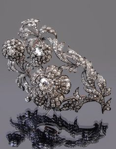 An early Victorian diamond floral en tremblant brooch, circa 1840. The old mine cut diamond set scrolled foliate brooch with three graduated mine cut and cushion cut diamond flower heads set en tremblant, in gold backed silver settings, the principal diamond estimated to weigh 3.03 carats, total diamond weight approximately 16.00 carats, 9.6cm long. #Victorian