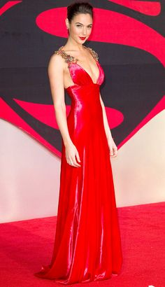 GAL GADOT in a red Prada dress with embellished straps and a matching lip for the Batman v Superman: Dawn of Justice premiere in London.