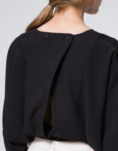 An elegant, lightweight top by Farrow in classic colors with minimal styling. Features round neckline, cropped sleeves, batsleeves, invisible stitching, tie waistband, back matching buttons, open back structure, cropped length and relaxed fit.  •	Lightw
