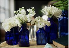 mixture of white flowers in blue glass bottles