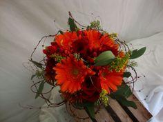 Hand Tied - Orange gerbera, vine collar, seeded euc., red roses, red hypericum berries, and solidago