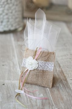 Μπομπονιέρα  βάπτισης πουγκί  λινάτσας με πλεκτό λουλουδάκι