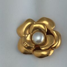 Authentic Chanel Camelia Pearl Brooch! Brooch is in very good condition.  Has some a spot where gold has come off.  Shown in pics.  Tiny when looked at with the naked eye. The brooch is about 2 1/2 inches wide and long. CHANEL Jewelry Brooches