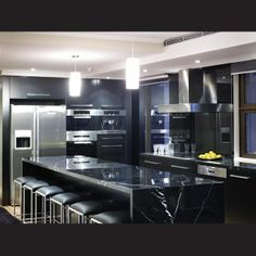 The highly reflective surfaces in this apartment kitchen include Nero Marquina solid marble benchtops and black lacquered cabinets. Three pe...