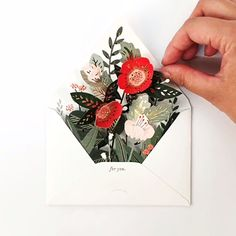 A laser-cut envelope containing a floral pop-up is nestled within a mailable envelope. Featuring gold foil and hidden message envelope.