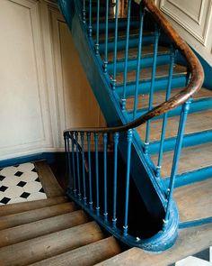 Esta sencilla joya, avivada con un azul intenso, da acceso a la vivienda. La bella curva que trazan barandilla y pasamanos es un diseño característico de los inmuebles antiguos de París.