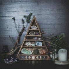 A small triangular shelf for stones and gems with the moon's phases painted on the bottom. Pine branches and candles on the wooden table are framing the stones - balance.