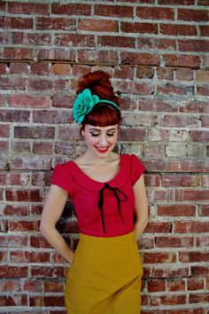 Teal head piece with red top. Hairdo and skirt give hints of 40's fashion.