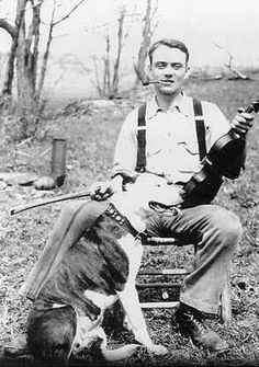 ( - p.mc.n. ) A fiddler and his Pit Bull enjoying some outdoor music.