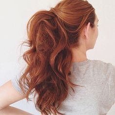 This hairstyle works best when your second-day hair is curly—no curling iron necessary! Pull your hair into a ponytail, leaving two front sections out. Take the left section and wrap it around the top of the ponytail, twisting as you go, and pin. No need to tuck the ends away to hide them! Repeat with the right section. Leaving the ends out gives the illusion of a thicker pony! Find a full tutorial with photos