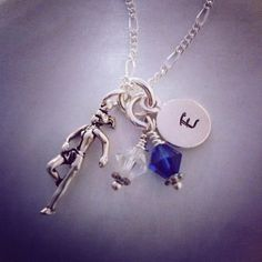 This running theme necklace is on a 16 silver plated chain and features a silver female runner charm, a hand stamped silver disc with initial