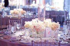 Stunning centerpieces with a glow of violet uplighting in the background. #AshByeventplanner #weddingdecor #weddingplanning #weddings #flowers
