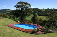 Above ground pool built into hill with deck