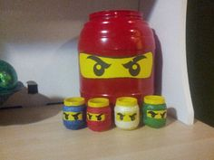 Ninjago Lego heads made from baby food jars, yellow spray paint, Sharpie, tissue paper and mod podge. The big one is an Utz cheeseball container. lego theme, lego birthday