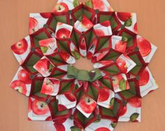 19 foldn stitch wreath done in cream bird Christmas print fabric accented with green and red fabric. Accented with a burlap bow and red bird.