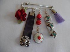 Broche épingle, habillée de rouge et violet, perles en verre pompon et fleur.