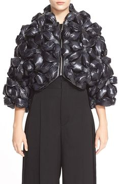 Texture - noir kei ninomiya Flower Motif Nylon Jacket $1235 Gathered, bunched and studded flowers with faux-leather centers create a showstopping 3D effect in this intricately constructed nylon jacket.