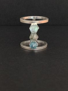 Hand cut aqua aura quartz crystal set into a handcrafted sterling silver ring.    Aqua aura quartz crystals are three varying shades. Ring is