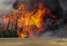 Smoke and flames from the wildfires erupt behind a car on the highway near Fort McMurray, Alberta, Canada, May 7, 2016. Among last year's extreme weather events were wildfires in Alberta, the costliest natural disaster in Canada's history.  REUTERS/Mark Blinch