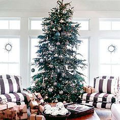 Christmas Casual    For a laidback look, dress your tree with shimmery lights and subtle blue bulbs. Surrounded by two brown-and-white stripe chairs and coordinating brown paper-wrapped gifts, this tree lends the room effortless warmth.    Tip: Place extra bulbs in a bowl for an easy centerpiece.  20 Charming Coastal Christmas Trees | Christmas Casual | CoastalLiving.com