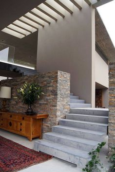 Cement stairs with kiaat treads lead from the entrance hall to the ...
