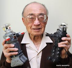 "Robert Kinoshita (February 24, 1914 – December 9, 2014). He is best known as the designer, of the B9 robot depicted in the 1960's TV series, Lost in Space. He is shown here, holding toy version of the B9 robot (left) as well as another he designed for the classic science fiction film, Forbidden Planet (""Robbie the robot""). So endearing was his design for ""Robbie"", that this robot was actually was cast in several movies, and made numerous appearances in TV shows throughout 1960's, and beyond."