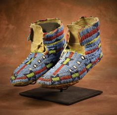 "Sioux Moccasins                                                  9"" long, fully beaded uppers in multicolored geometric designs on blue field with hard soles, on native tanned hide. Fine condition, c 1880"