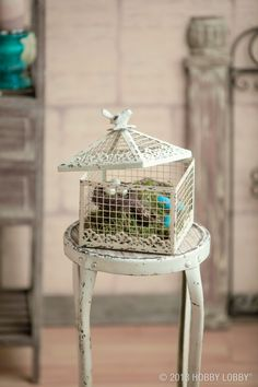 This small-scale birdcage is big on style! On  the inside we added springy moss,  looks-like-the-real-deal eggs (we  painted the blue ones) and even  two tiny nests.