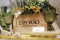 Sobre o centro da mesa, temperos em uma caixa de vinho em madeira.