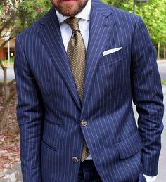 The pinstripe blue jacket and the gold tie go so well together
