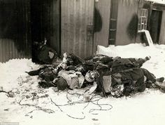 Dead German soldiers in France are seen piled and frozen in the winter weather (December 1944). Photographed by Brigadier General Charles Day Palmer