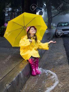 Young girl playing in the rain with yellow umbrella Stock Photo Yellow Umbrella, Rain Umbrella, Under My Umbrella, Walking In The Rain, Singing In The Rain, I Love Rain, Weather Activities, Rain Photography, Going To Rain