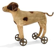 A STEIFF SMALL VELVET POINTER ON WHEELS, (1414), white with brown spots, black boot button eyes, brown stitching, gold painted cast-metal wheels and FF button, circa 1908 --6in. (15.5cm.) long (discoloured and slight wear) Price Realized (Set Currency)   £ 525 ($ 831)