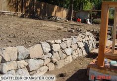 Retaining wall with rock in your landscapeing yard.  In Redmond call 425-736-5185