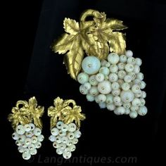 Nothing short of spectacular, the pin alone overflows with an abundance of opals that are perfectly matched. 18K yellow gold pin and earring set in a grape cluster motif dripping with opals and golden grape leaves, circa 1950s. The pin measures 2 X 3 1/4 and the earrings measure 3/4 X 1 3/4.