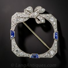Already gift wrapped with a bow on top, a classic platinum and diamond wreath brooch with a stylish Art Deco twist. Instead of the usual circular design, Art Deco geometry is employed along with 1.35 carats of sparkling white diamonds and vibrant blue French-cut calibre sapphire accents in this distinctive and distinguished adornment dating from the 1920s-30s. 1 3/8 inches high by 1 1/4 inches wide.
