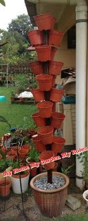 """Vertical planting tower- attached pots are """"holders"""" for your actual potted plants. would love to try growing strawberries like this!"""