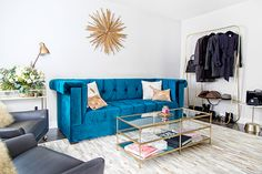 Blue and gold living room features a gold sunburst clock by Z Gallerie placed over a custom made sapphire blue velvet tufted sofa placed next to a wood and brass vintage bar cart, West Elm Terrace Bar Cart, and Industrial Task Table Lamp.