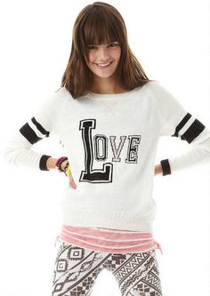 Crew neck pullover with love intarsia and varsity striped sleeves and hi low hem.