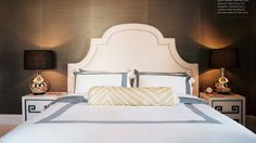 Love all the geometry - curves of the headboard, crisp bedding, round lamp bases, greek key detail...