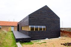 Fabulous Modern Barn Converted Into Homes Design With Black Wall Siding And Stylish Glass Window And Wide Wooden Terrace Design. .
